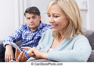Unhappy Man Sitting On Sofa As Partner Uses Mobile Phone