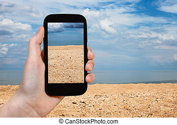 shelly and sand beach of Azov Sea on smartphone - travel...