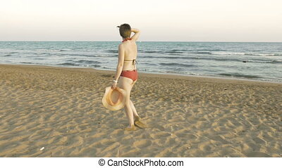 A female is walking on the sand in bathing suit - A great...