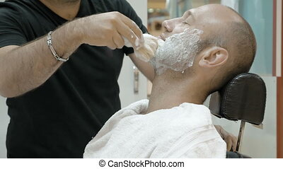 A man is sitting at a barber's shop to get groomed. The...