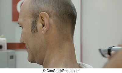 Barber is shaving his client's neck with shearer - Barber is...