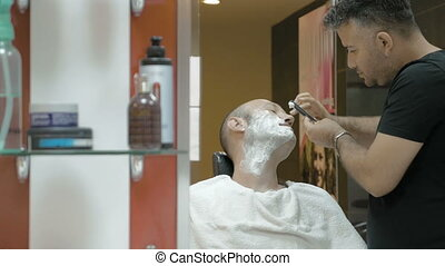 Barber is shaving his client in old fashion manner - The...