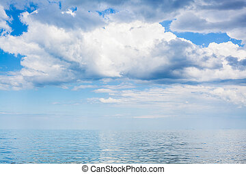 clouds in blue sky over calm water of Azov Sea - white...