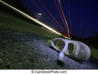 Accident Shoe - Night shot of a childs shoe after a car...