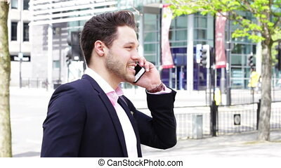 Using a Smartphone in the City - Business man in the city....