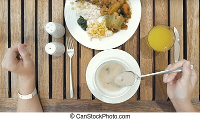 Lady is using utensils to cut meal in small bites - The lady...