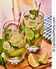On wooden boards is glasses with mohito and napkin. -...