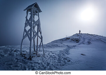 Lone man on the top of the mountain in winter