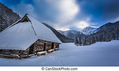 Old wooden hut in winter mountains