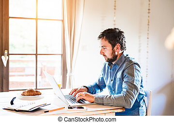 Man sitting at desk working from home on laptop - Man...