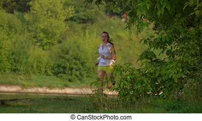 Brunette girl running on sandy summer riverside. 4K...
