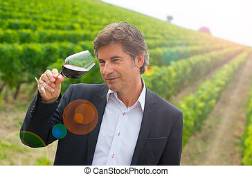 Portrait confidant vintner drinking red wine in winery...