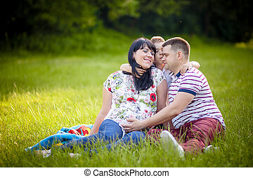 Happy beautiful family with their pregnant mother outdoors at the park