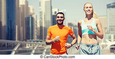 couple running over dubai city street background - fitness,...