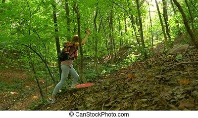 Brunette girl hiking uphill in sunny forest. 4K steadicam...