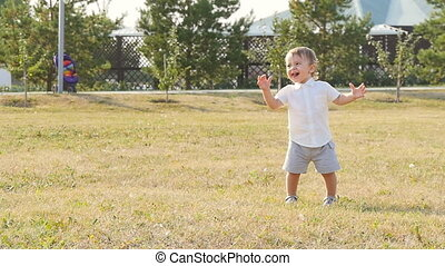 Young happy little boy smiling greeting someone in the park...