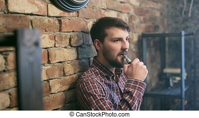 Handsome young man smoking electric e cigarette vapor...