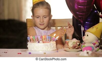 Girl blows out the birthday cake at the table with gifts -...