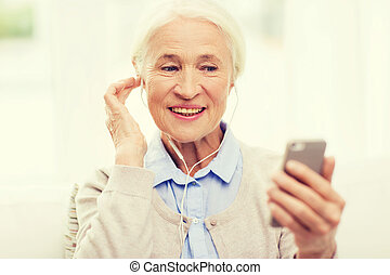 senior woman with smartphone and earphones at home -...