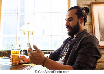 man with smartphone drinking beer at bar or pub - people and...