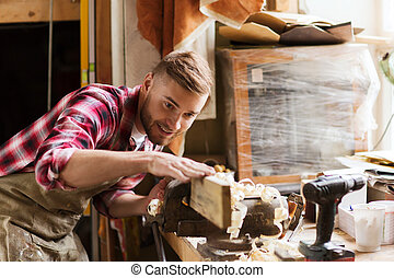 carpenter working with wood plank at workshop - profession,...