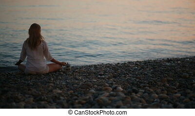 young woman practicing yoga on the beach at sunset. calm sea...
