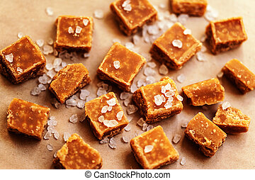 Sweet caramel candies background. Salted caramel pieces and...