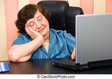 Bored elderly woman in office