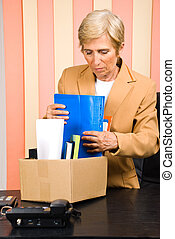Senior retired collect her belongings in a box - Senior...