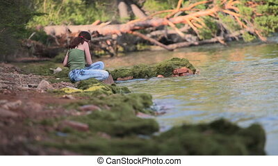 Girl sits on the shore of Baikal - Girl sits on the shore of...