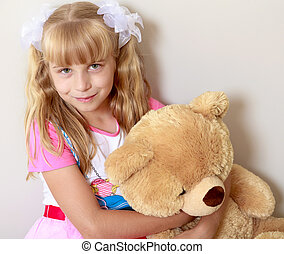 Girl with a Teddy bear - Happy little girl hugging his neck...