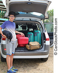 young boy loaded the trunk of the car before departure