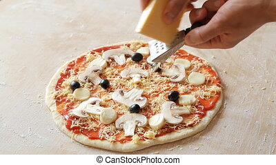 Grate cheese over tasty pizza.