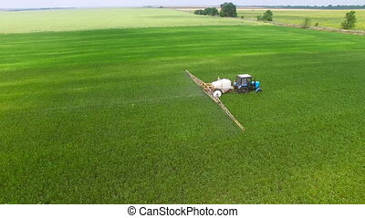 Tractor sprinkles bean field - Tractor in a field spray the...