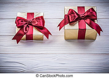Wrapped giftboxes on wooden board directly above holidays...
