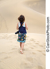 Woman on desert sand - Young woman carries a camera through...