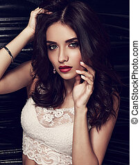 Beautiful bright evening makeup female model posing in white fashion white top on black background