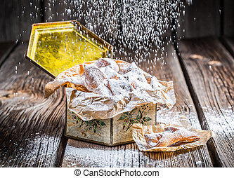Falling powdered sugar on angel wings in box