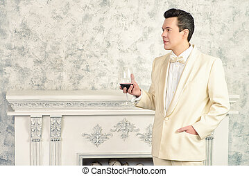 a man drinks cognac - Handsome well-dressed mature man in...