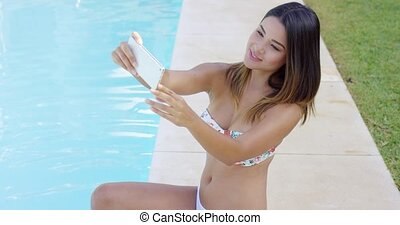Pretty young woman posing for a selfie at the pool