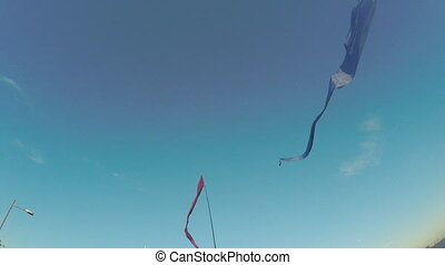 Fluttering ribbons on flagpoles - Several of colored ribbons...