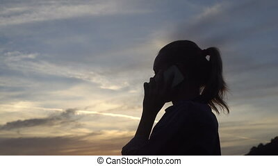 Silhouette of happy woman talking on the mobile phone during beautiful sunrise