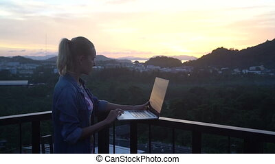 Pretty blonde woman working on a laptop while standing on a rooftop over beautiful sunrise