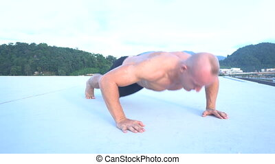 Fitness sport man doing clap push-ups outside on a rooftop -...
