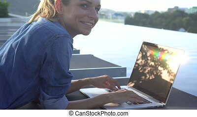Pretty blonde woman working on a laptop while lying on sunbed with man swimming in infinity pool background