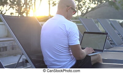 Outdoors portrait of handsome young man working on a laptop...