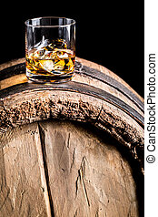 Whiskey glass with ice on old wooden barrel
