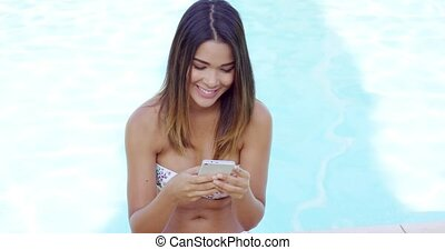 Smiling young woman reading a text message on her mobile as...