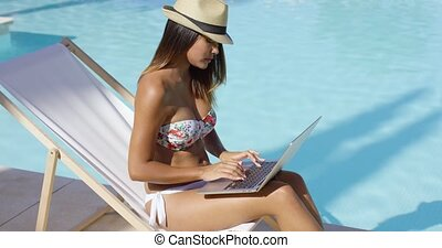 Sexy young woman relaxing at the swimming pool sitting in a...