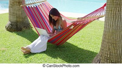 Smiling woman using laptop in hammock - Single smiling woman...